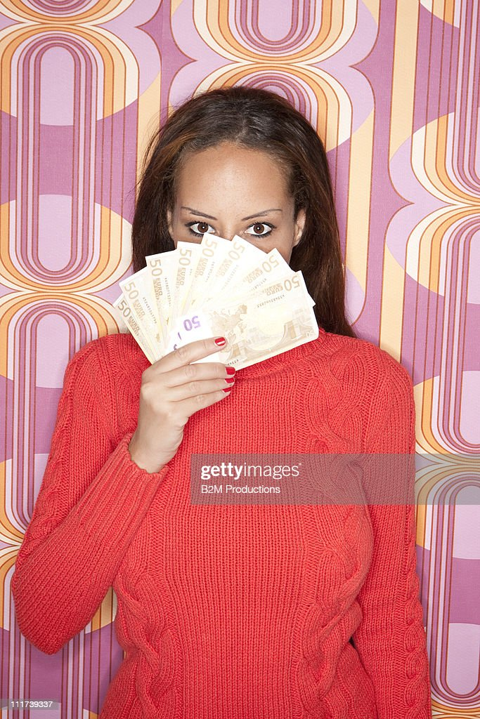 Woman covering lips with money : Stock Photo