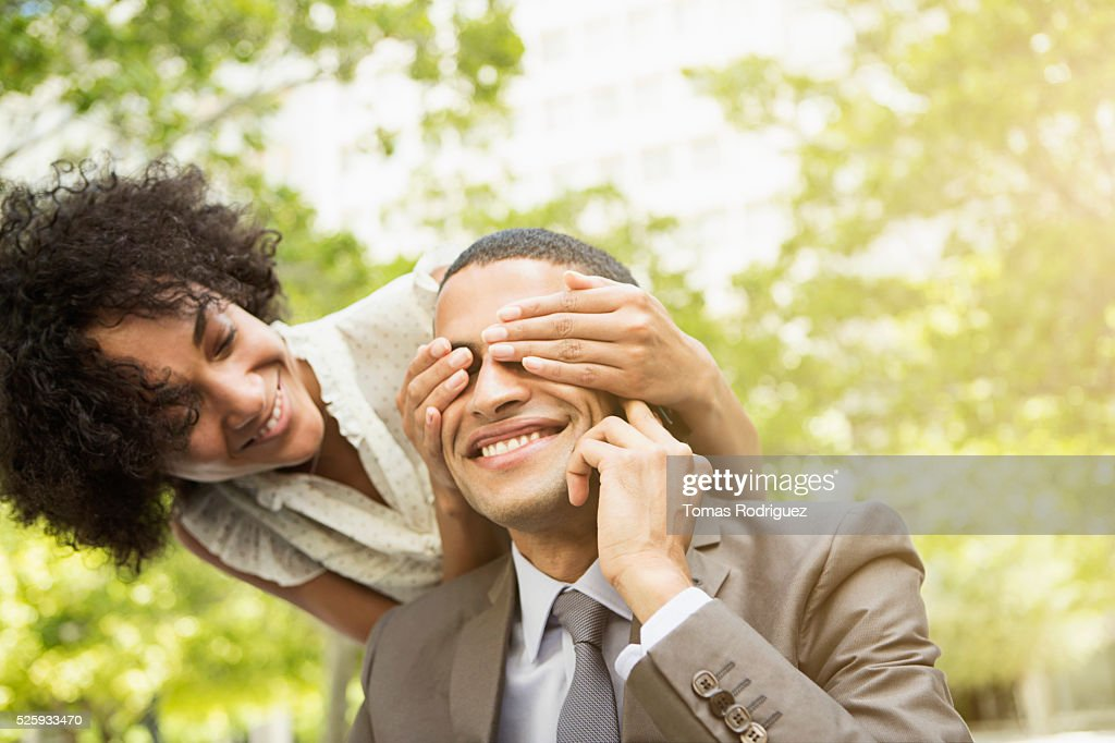 Woman covering mans eyes : Stockfoto