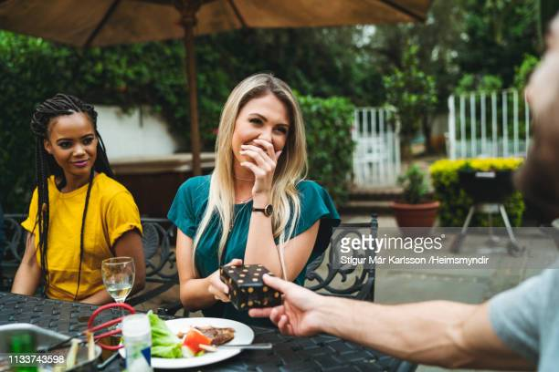 woman covering mouth while receiving gift by man - giving stock pictures, royalty-free photos & images