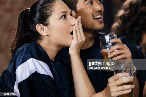 woman covering mouth while watching soccer match with friend in bar - fan enthusiast stock pictures, royalty-free photos & images
