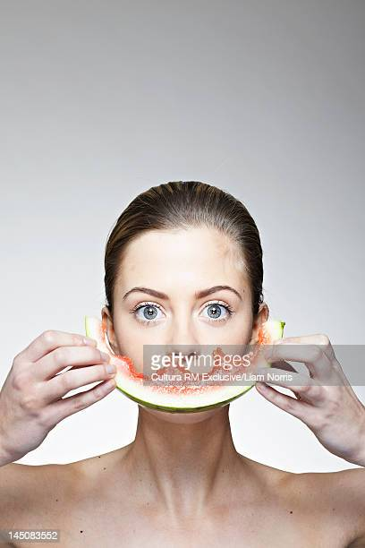 Woman covering mouth with watermelon