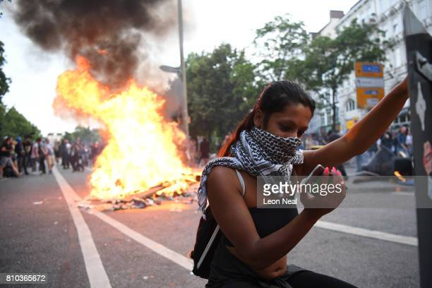 A woman covers her face and checks her mobile phone as a fire burns in the middle of town during an antiG20 protest on July 7 2017 in Hamburg Germany...