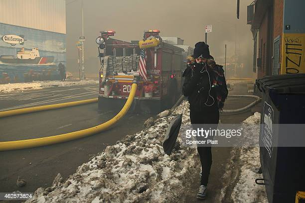 A woman covers her face as Fire Department of New York firefighters work to contain a building fire that went to six alarms at the CitiStorage...