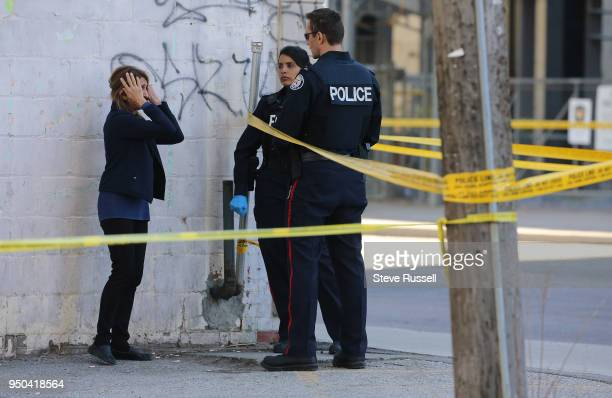 TORONTO ON APRIL 23 A woman covers her face as Police have Yonge Street blocked off at Parkview Avenue where on of the victims lies on the East side...