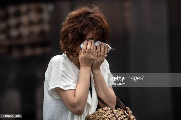 A woman covers her face as she cries near the Kyoto Animation Co studio building after an arson attack on July 19 2019 in Kyoto Japan Thirty three...
