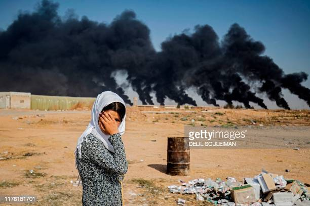 TOPSHOT A woman covers her face as she stands along the side of a road on the outskirts of the town of Tal Tamr near the Syrian Kurdish town of Ras...