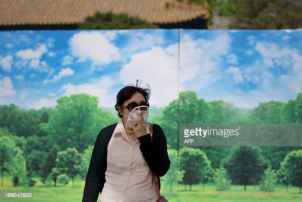 A woman covers her face as she walks past a billboard at the Forbidden City in Beijing on May 19 2013 China will more than double the number of...