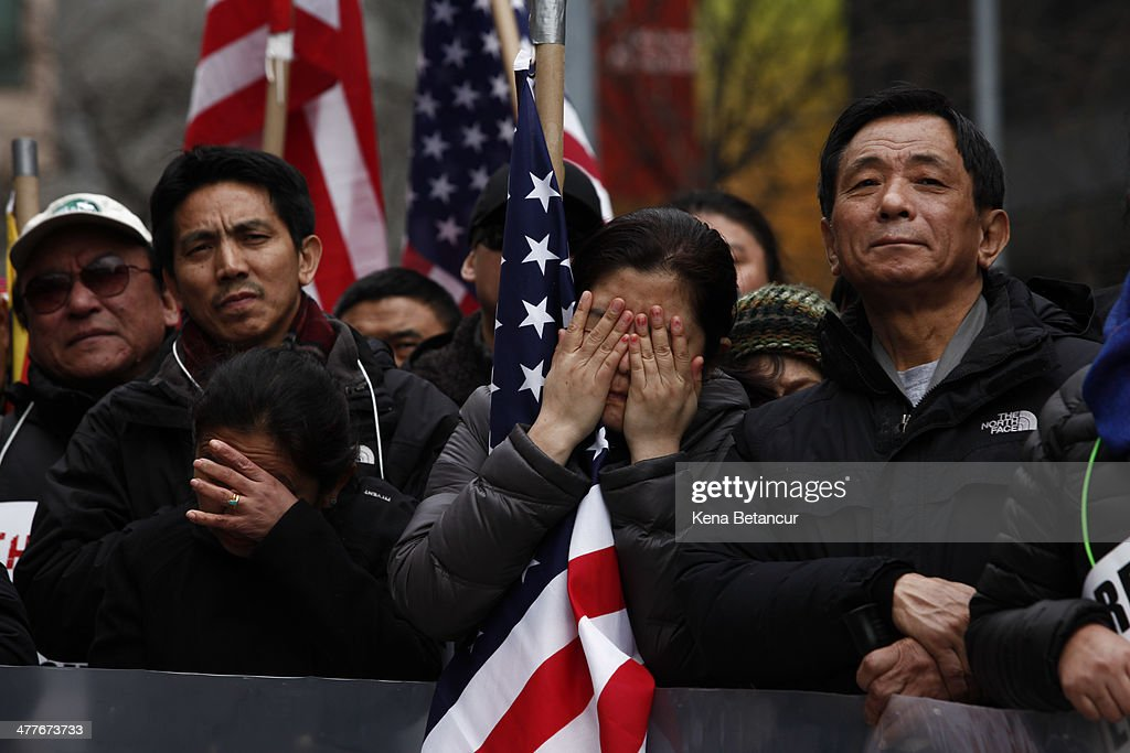 A woman covers her face at a rally to mark the 55th anniversary of the Tibetan national uprising outside United Nations building on March 10, 2014 in New York City. On this day in 1959, an uprising against China's occupation of the autonomous region of Tibet took place, forcing spiritual leader the Dalai Lama to flee into exile.