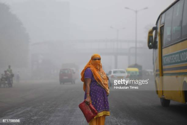 A woman covers her face to avoid pollution amid heavy smog on November 8 2017 in New Delhi India Delhi was enveloped in a thick blanket of haze for...