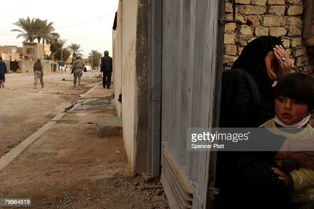 A woman covers her face while holding a child February 24 2008 in Diyala Province Baquba Iraq Baquba was until recently the geographical headquarters...