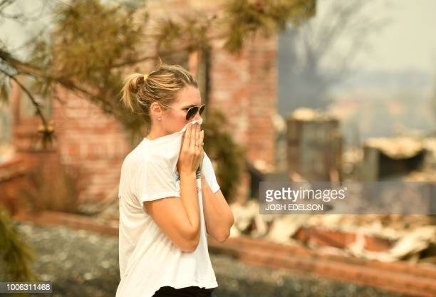A woman covers her face while viewing her grandmother's burned home during the Carr fire in Redding California on July 27 2018 Two firefighters have...