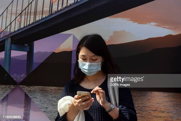 A woman covers her face with a sanitary mask as she uses her smartphone after the first cases of coronavirus have been confirmed in Hong Kong China...