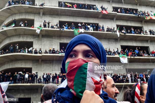 A woman covers her face with the national flag as Algerian protesters demonstrate in the capital Algiers against ailing president's bid for a fifth...