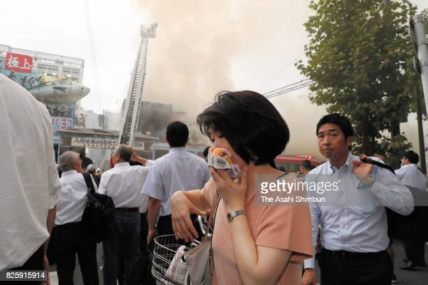 A woman covers her face with towel walks past the fire site outside Tokyo's famed Tsukiji fish market on August 3 2017 in Tokyo Japan The blaze in...