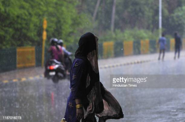 Woman covers her head with a cloth during heavy rains, on July 21, 2019 in Noida, India. The minimum temperature was recorded at 28.8 degrees...