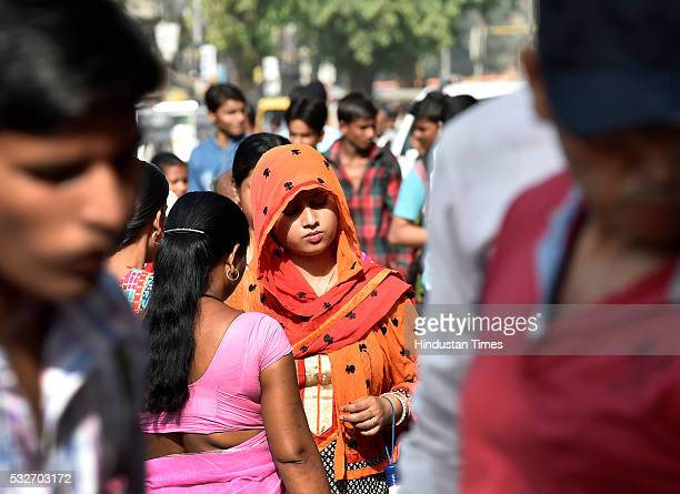 A woman covers her head with dupatta to protect herself from the scorching heat outside Gurdwara Sis Ganj on a hot summer day on May 19 2016 in New...