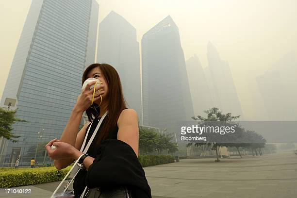 Woman covers her mouth and nose with a face mask as she walks past the central business district of Singapore, on Friday, June 21, 2013. Singapore's...