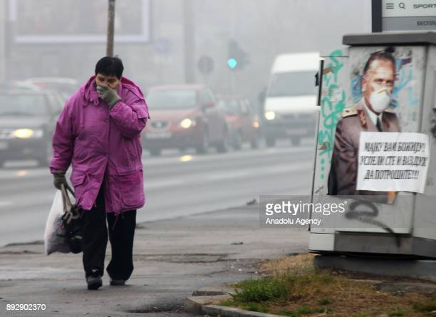 A woman covers her mouth and nose with her hand as she is walking through the street during heavy fog and smog cover Skopje and air pollution levels...