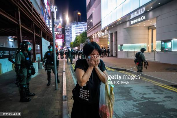 Woman covers her mouth as riot police fire pepper ball projectiles during a rally against a new national security law, on the 23rd anniversary of the...