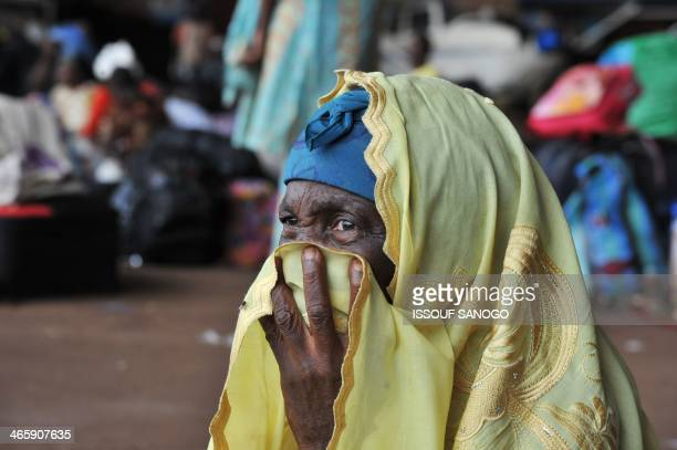 A woman covers her mouth with her head scarf as displaced Central African and Chadian Muslims fleeing attacks by Christian extremist militias sit in...