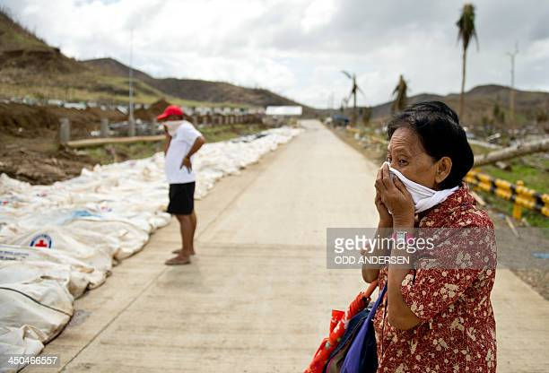 A woman covers her nose and mouth as she stopped to look at the body bags containing the remains of some 170 dead collected from the rubble at the...