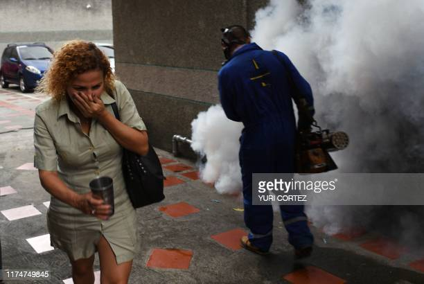 Woman covers her nose as she walks past a municipal worker fumigating against the aedes aegypti mosquito, vector of dengue fever, Zika fever and...