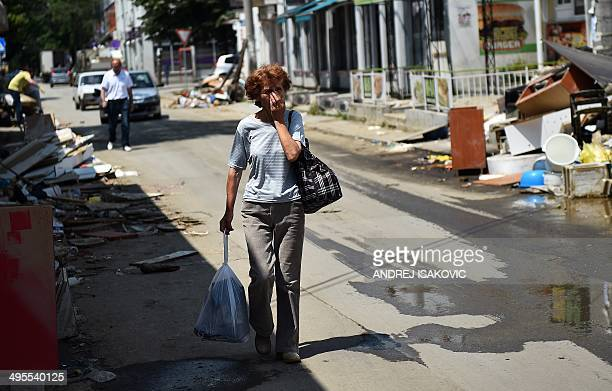 A woman covers her nose as she walks past trash in a street in the town of Obrenovac 40 kilometers west of capital Belgrade on June 4 2014 Serbian...