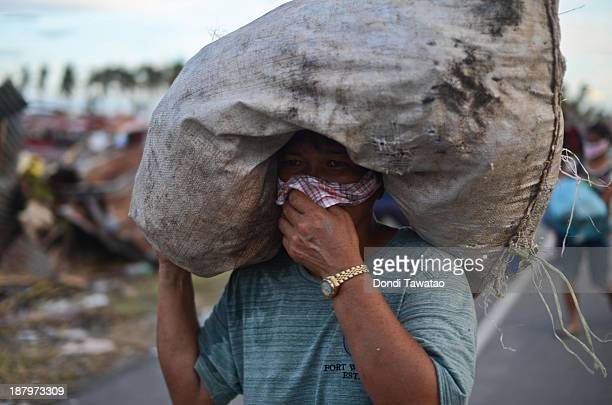 A woman covers her nose from the stench of dead bodies lying on the street in Tacloban City on November 14 2013 in Tacloban Philippines Typhoon...