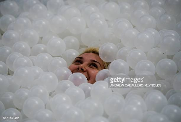 A woman covers herself in plastic balls at 'The Beach' art installation at the National Building museum in Washington DC on September 6 2015 The...
