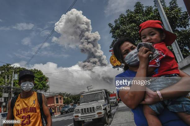 A woman covers the face of a child as Mount Mayon spews a huge column of ash noon in Camalig Albay province Philippines January 24 2018 Mount Mayon...
