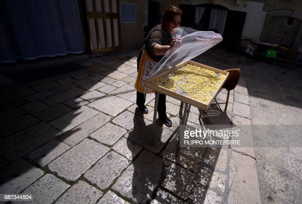 A woman covers traditional orecchiette homemade pasta in the historic center of Bari on May 12 2017 G7 finance ministers met today in Bari looking...