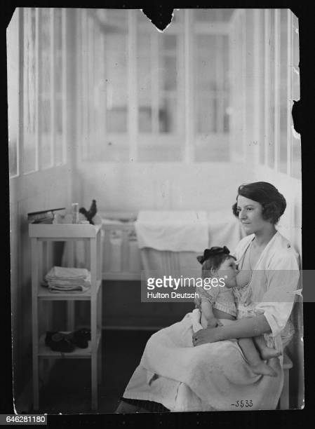 A woman cradles her child in her lap as she feeds