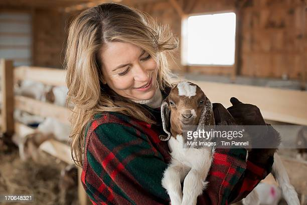 A woman cradling a young goat kid in her arms, on a farm.