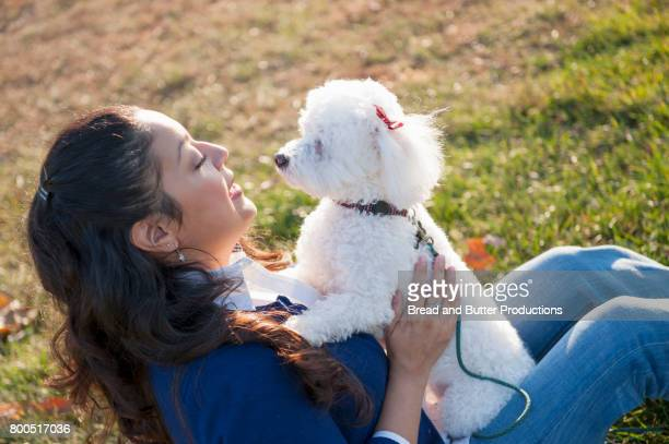 woman cradling mini poodle dog, looking at each other - miniature poodle stock photos and pictures