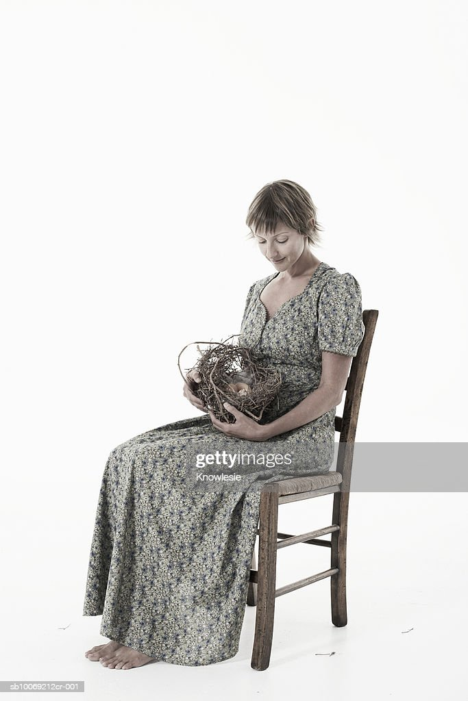 Woman cradling nest with eggs against white background : Stockfoto