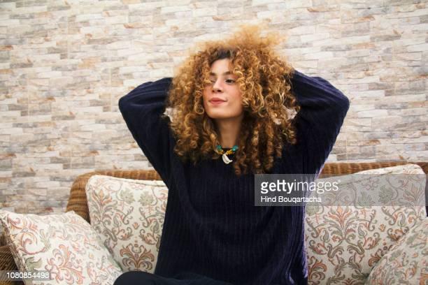 jeune femme joue avec ces cheveux bouclés - showus stockfoto's en -beelden