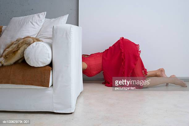 Woman crawling behind sofa, low section, side view