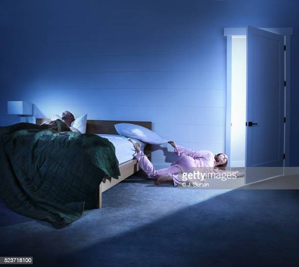 Woman crawling out of bed away from her snoring husband