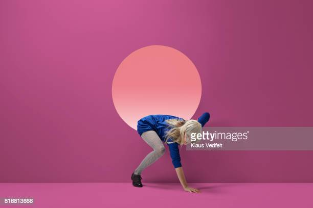 woman crawling out of round opening in coloured wall - caucasian appearance stock pictures, royalty-free photos & images