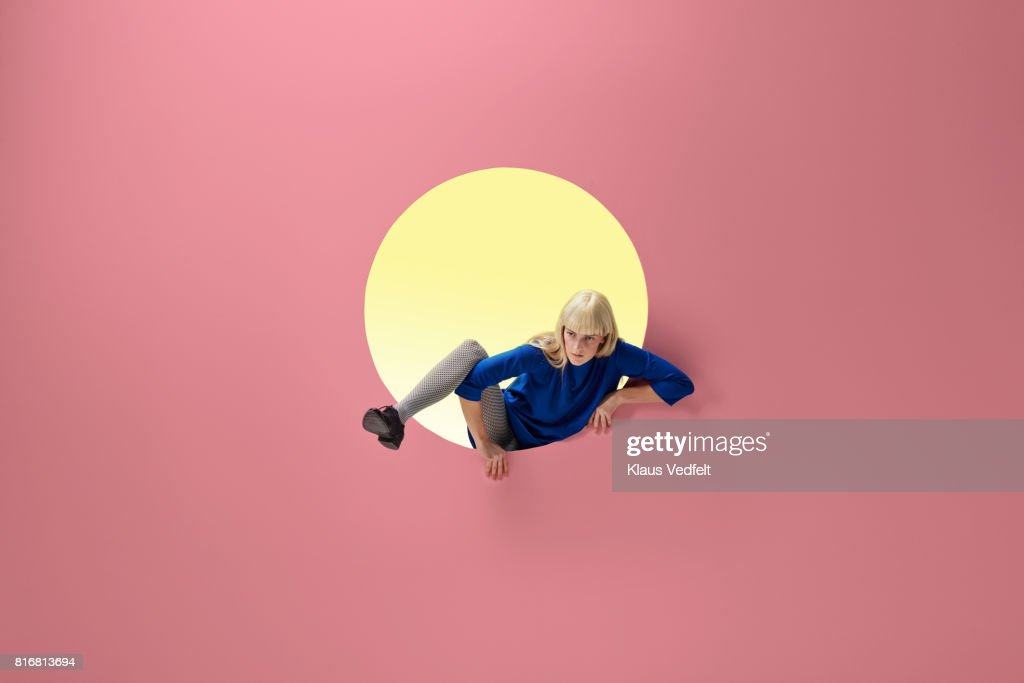 Woman crawling out of round opening in coloured wall : Stock Photo