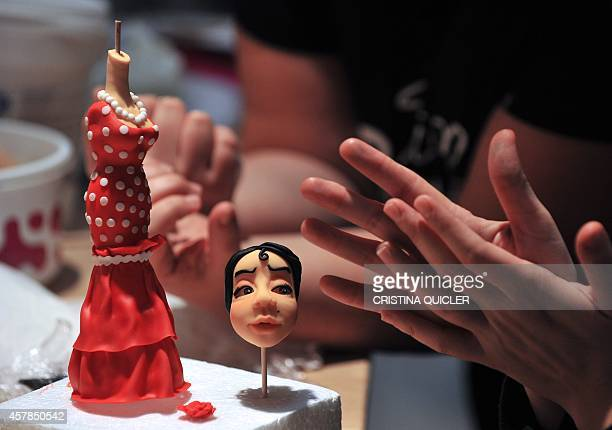 A woman creates a flamenco doll made from sugar to decorate a cake during the Sevilla creative pastry sweet fare at Fibes in Sevilla on October 25...