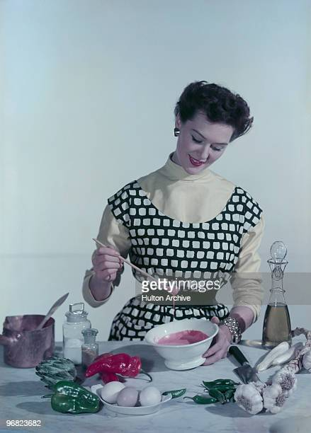 A woman creates a piquant sauce from fresh ingredients circa 1955