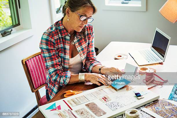 A woman creating a collage picture with material and paper.