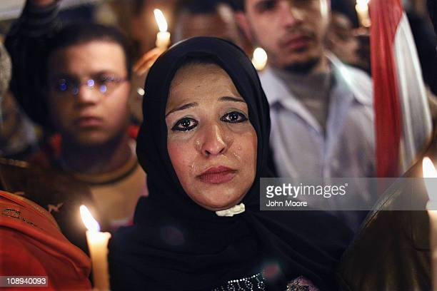 A woman cries as antigovernment protesters walk during a candlelight vigil for those killed during the uprising in Tahrir Square on February 9 2011...
