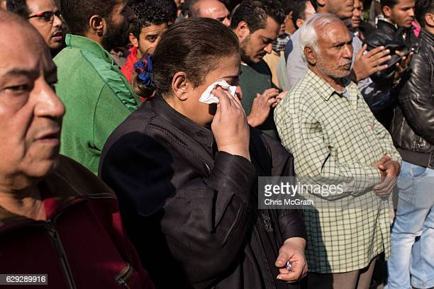 A woman cries as Christians pray in the street outside the orthodox church of the Virgin Mary during the official funerals for victims of yesterdays...