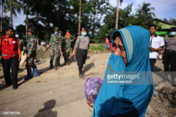 TOPSHOT A woman cries as Indonesian search and rescue personnel work in the background in Manuju subdistrict Gowa regency South Sulawesi on January...