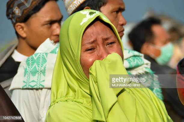 TOPSHOT A woman cries as people look at the damages after an earthquake and a tsunami hit Palu on Sulawesi island on September 29 2018 Rescuers...