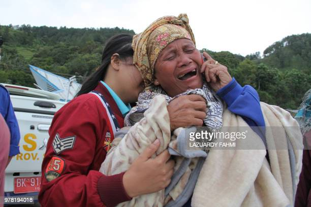 A woman cries as she finds out her family are listed as missing at the Lake Toba ferry port in the province of North Sumatra on June 19 after a boat...