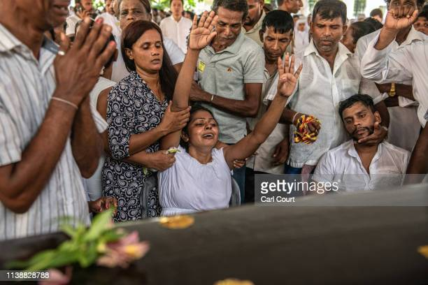 A woman cries as she gestures towards a coffin during a mass funeral at St Sebastian's Church on April 23 2019 in Negombo Sri Lanka At least 311...