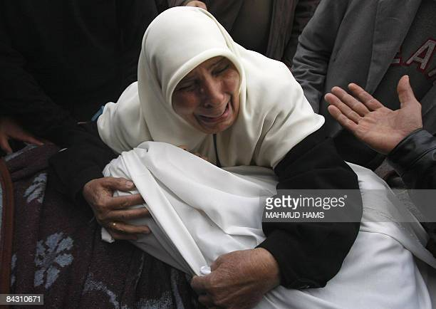 A woman cries as she holds the body of one of her relatives at the mortuary of AlShifa hospital on January 16 2009 Israel's offensive on Gaza...